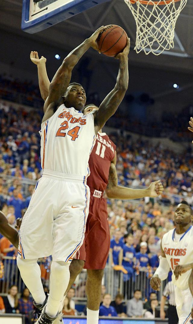 Florida guard Florida forward Casey Prather (24) gets past Alabama forward Shannon Hale (11) as he goes to the basket during the first half of an NCAA college basketball game Saturday, Feb. 8, 2014, in Gainesville, Fla. (photo by Phil Sandlin)
