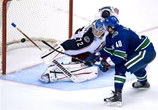 Vancouver Canucks' Maxim Lapierre (40) sends a shot past Columbus Blue Jackets goalie Sergei Bobrovsky (72) in a shootout during NHL hockey action in Vancouver, British Columbia, Tuesday, March 26, 2013. (AP Photo/The Canadian Press, Jonathan Hayward)
