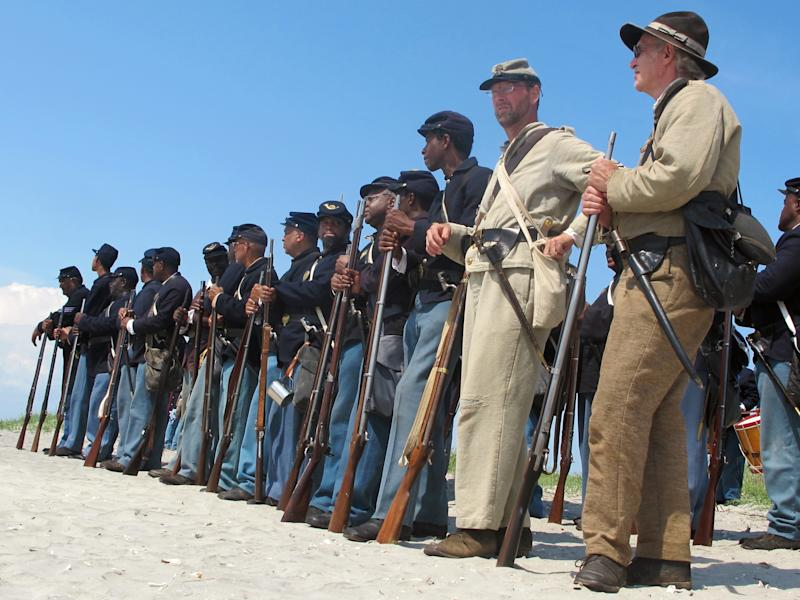 """Re-enactors representing both North and South stand on Morris Island near Charleston, S.C., on Thursday, July 18, 2013 during a observance of the 150th anniversary of the charge of the black 54th Massachusetts Volunteer Infantry in a fight commemorated in the film """"Glory."""" (AP Photo/Bruce Smith)"""