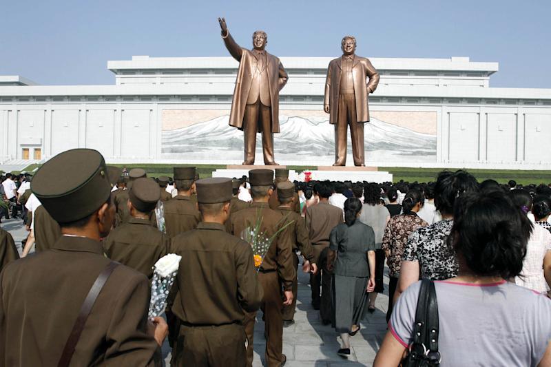 North Koreans visit the statues of late leaders Kim Il Sung, left, and Kim Jong Il, right, on Sunday, July 8, 2012, on Mansu Hill in Pyongyang, North Korea, to pay tribute to Kim Il Sung on the 18th anniversary of the former North Korean leader's death. (AP Photo/Kim Kwang Hyon)