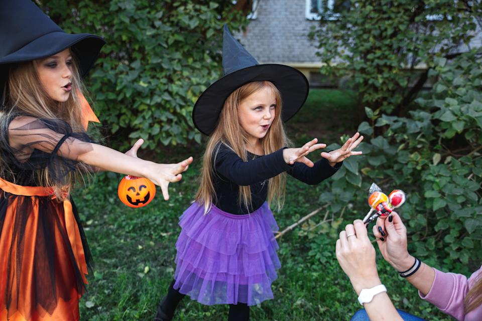 Little children trick or treating. Two little witches on Halloween