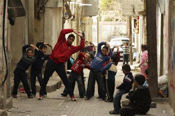 Gaza runner Bahaa al-Farra stretches during a training session as children mimic him while posing for the camera in Shati refugee camp in Gaza City, March 25, 2012.