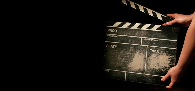 Movie clapperboard being held against a dark background.