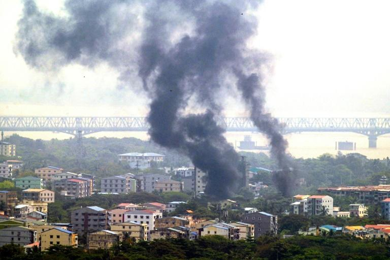 Smoke rises over Thaketa township in Yangon on March 27, 2021, as security forces pursue their crackdown on protests