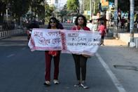 "Two young women hold up their gamosas, emblazoned with ""Mr Modi, Assam is not your dumping ground"" in English and Assamese, the local official language"