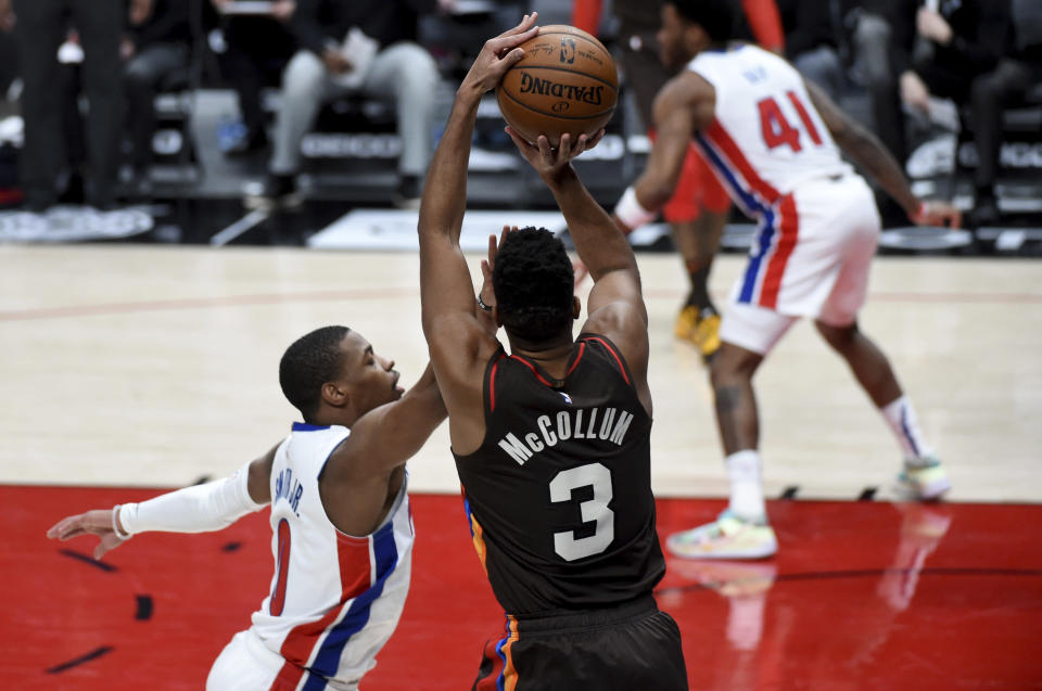 Portland Trail Blazers guard CJ McCollum (3) hits a shot over Detroit Pistons guard Dennis Smith Jr., left, during the second half of an NBA basketball game in Portland, Ore., Saturday, April 10, 2021. The Blazers won 118-103. (AP Photo/Steve Dykes)