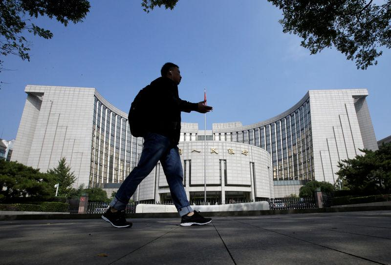 FILE PHOTO: A man walks past the headquarters of the People's Bank of China (PBOC) in Beijing