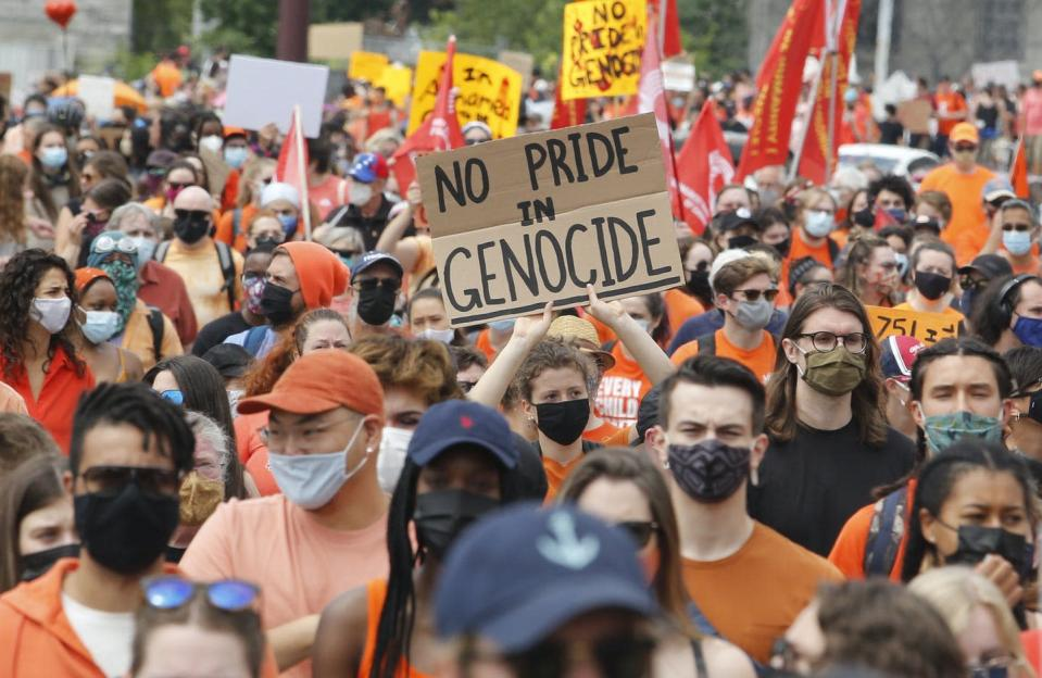 A crowd wearing orange marches down the street, a sign reads 'no pride in genocide'