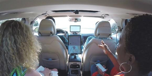 Two passengers in a self-driving car with test driver.