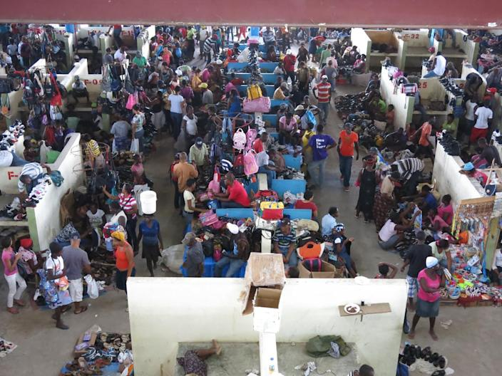 FILE - In this July 15, 2013 file photo, Haitians and Dominicans gather at a market in the border town of Dajabon in the Dominican Republic. The Dominican Republic's top court on Thursday, Sept. 26, 2013 stripped citizenship from thousands of people born to illegal migrants, a category that overwhelmingly includes Haitians brought from their neighboring homeland to work on farms. The decision cannot be appealed, and it affects all those born since 1929. (AP Photo/Ezequiel Abiu Lopez, File)