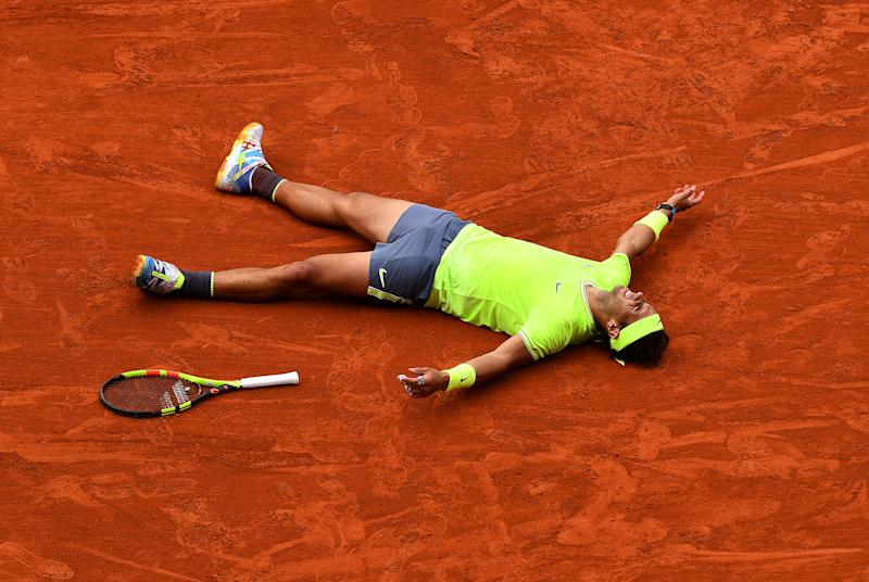 Rafael Nadal falls to the ground and celebrates match point.