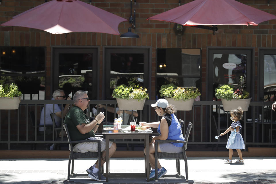 FILE - In this July 18, 2020, file photo patrons eat at table set up on a sidewalk in Burbank, Calif. The pandemic began with devastation in the New York City area, and was followed by a summertime crisis in the Sun Belt. But it is now striking cities with much smaller populations, often in conservative corners of America where anti-mask sentiment runs high, creating problems at hospitals and schools in the Midwest and West. (AP Photo/Marcio Jose Sanchez, File)