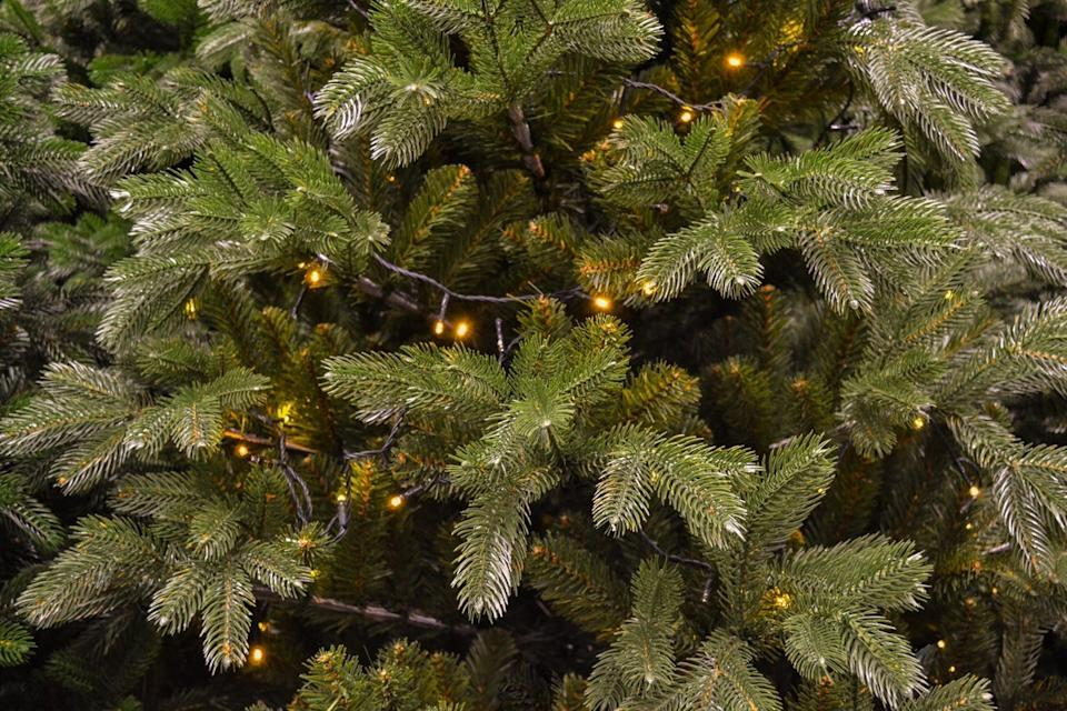 Close-up of the branches of an artificial green Christmas tree with a garland of yellow Christmas lights. Christmas holiday background