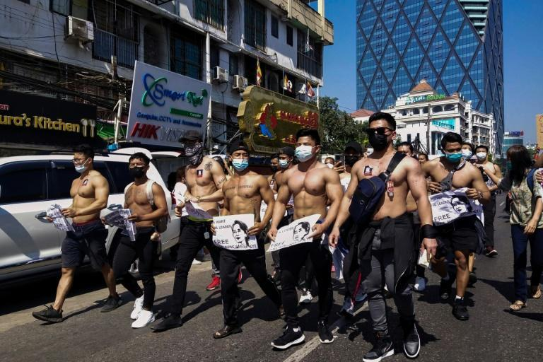 The shirtless men held signs calling for the release of detained civilian leader Aung San Suu Kyi