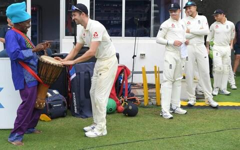 Mark Wood of England plays the drum of an entertainer dressed in traditional attire as captain Joe Root and team mates look on - Credit: Stu Forster/Getty Images