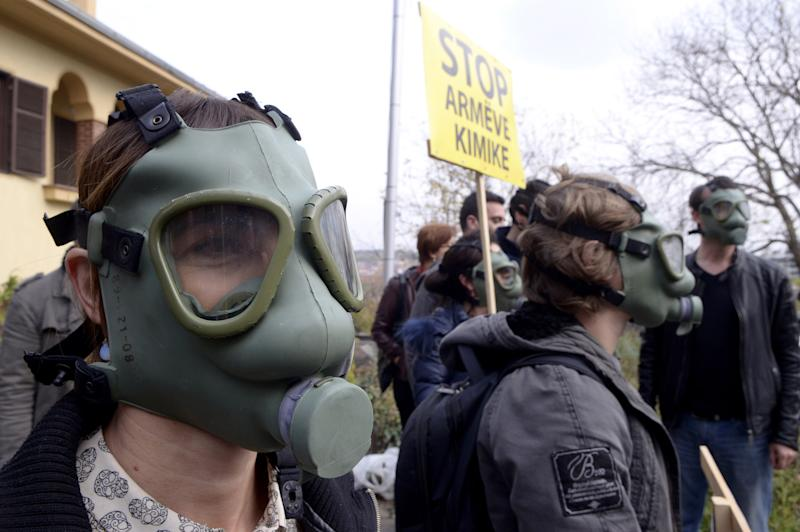 """People wearing gas masks and posters reading """"Stop to the chemical weapons"""" during a protest in front of the Albanian Embassy in Skopje, Macedonia, on Thursday, Nov. 14, 2013. The protests in Macedonia are supporting separate protest groups in nearby Albania, who reject plans to destroy Syrian chemical weapons in Albania. (AP Photo/Boris Grdanoski)"""