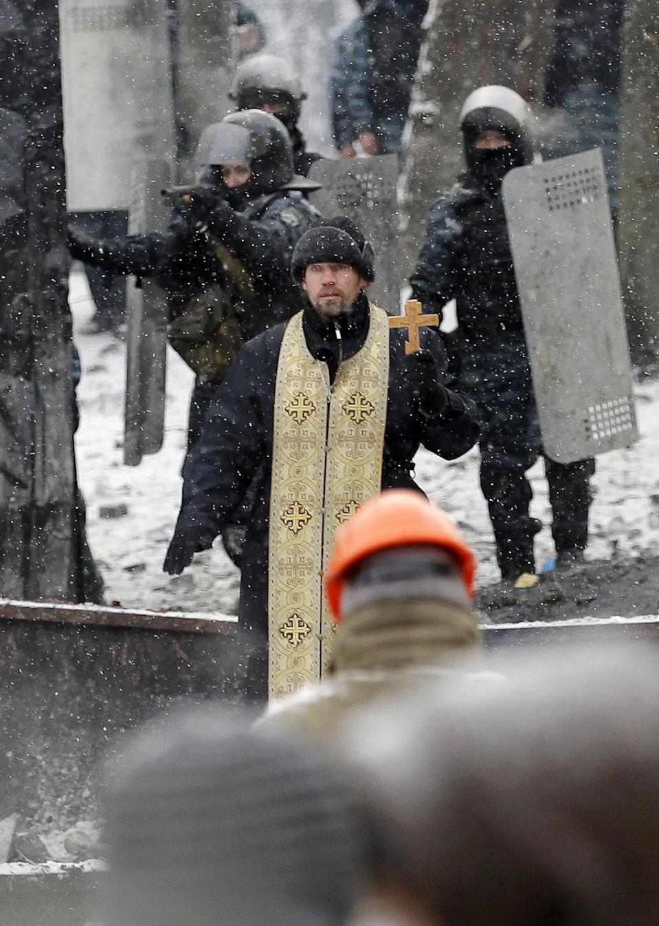 In this file photo taken on Wednesday, Jan. 22, 2014, An Orthodox priest prays as he stands between pro-European Union activists and police lines during clashes in central Kiev, Ukraine. As a barricade of blazing tires belched thick black smoke, a line of priests stood between angry protesters and ominous riot police. Every freezing morning, priests sing prayers to demonstrators gathered on the Ukrainian capital's main square, a solemn and soothing interlude to vehement speeches calling for revolution. (AP Photo/Darko Vojinovic, file)