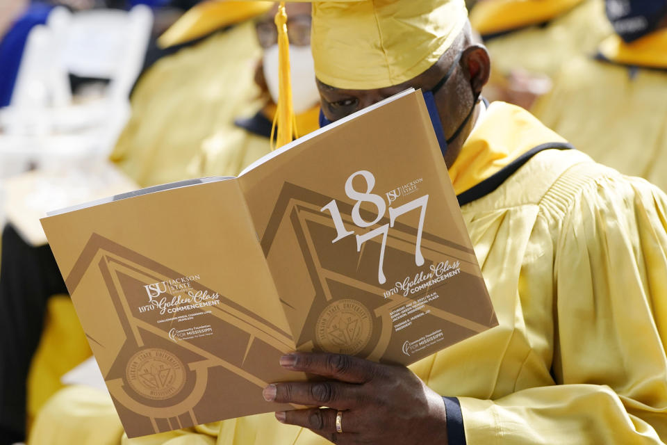 A Jackson State member of the Class of 1970 reads the commemorative program prior to being one of 74 graduates honored by the historically Black university, with an official graduation ceremony, Saturday, May 15, 2021, in Jackson, Miss. The ceremony was held 51 years after the school canceled its 1970 graduation ceremony after white law enforcement officers marched onto campus near the end of the spring semester and violently suppressed protests against racism with gunfire, killing two and wounding 12. (AP Photo/Rogelio V. Solis)