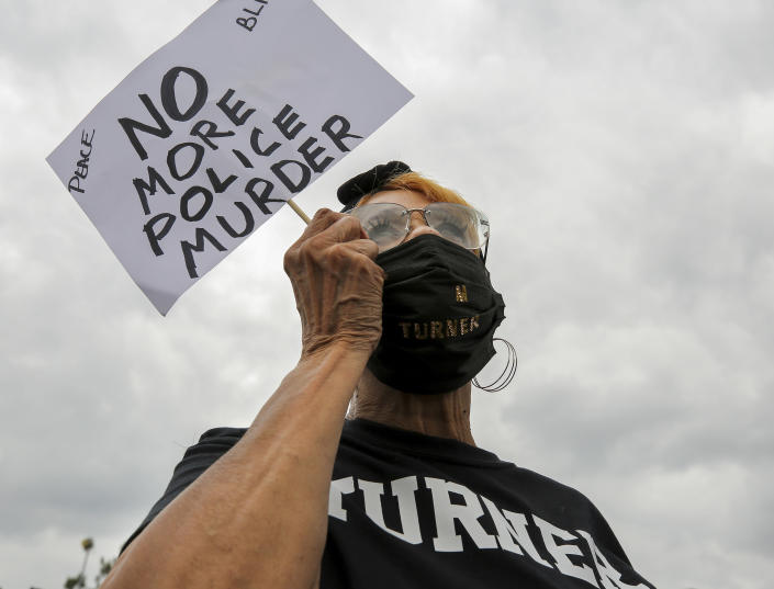 """Linda Magwood holds up a sign as she listens to speakers during a """"Justice for Pamela Turner"""" rally on the two-year-anniversary of Turner's death, Thursday, May 13, 2021, in Baytown, Texas. Turner was fatally shot in 2019 by a police officer in the Houston suburb after a struggle over his stun gun. (Godofredo A. Vásquez/Houston Chronicle via AP)"""