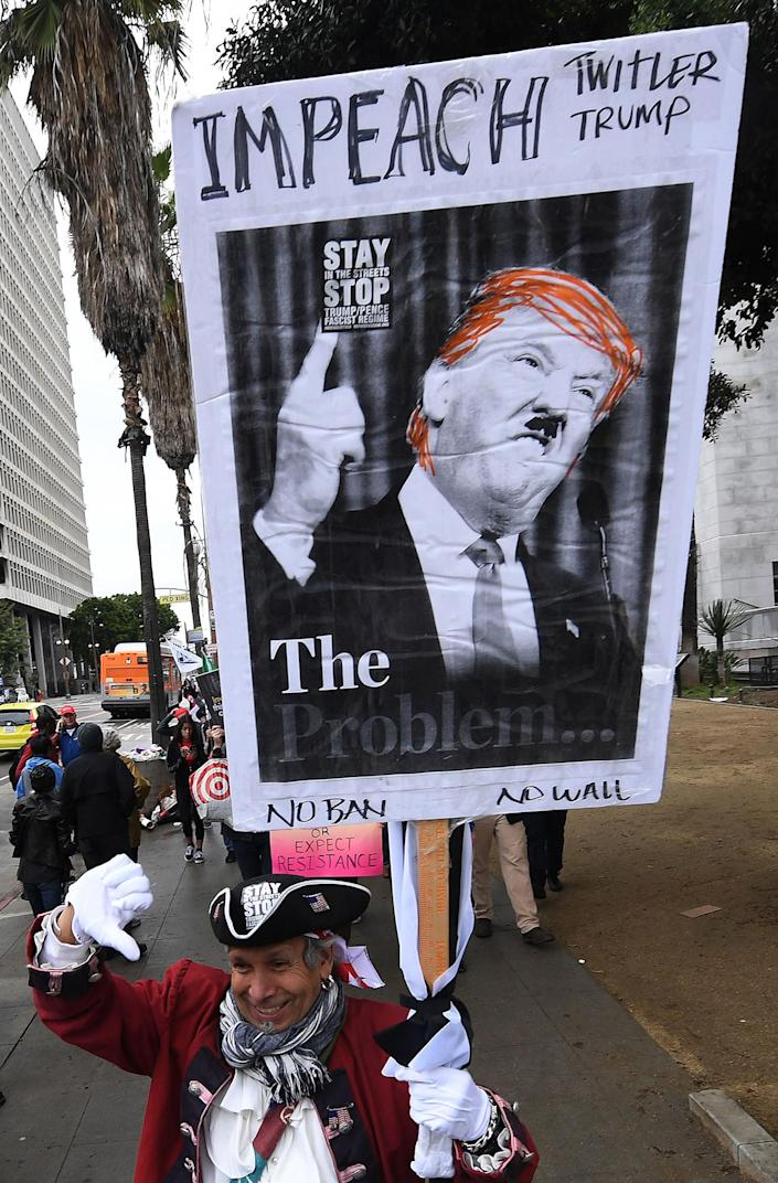 <p>Protesters carry anti-Trump signs during a 'Not My President Day' demonstration outside City Hall in Los Angeles on Feb. 20, 2017. (Mark Ralston/AFP/Getty Images) </p>