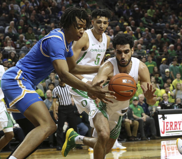 UCLA's Moses Brown, left, battles Oregon's Miles Norris and Ehab Amin, right, for the ball during the first half of an NCAA college basketball game Thursday, Jan 10, 2019, in Eugene, Ore. (AP photo/Chris Pietsch)