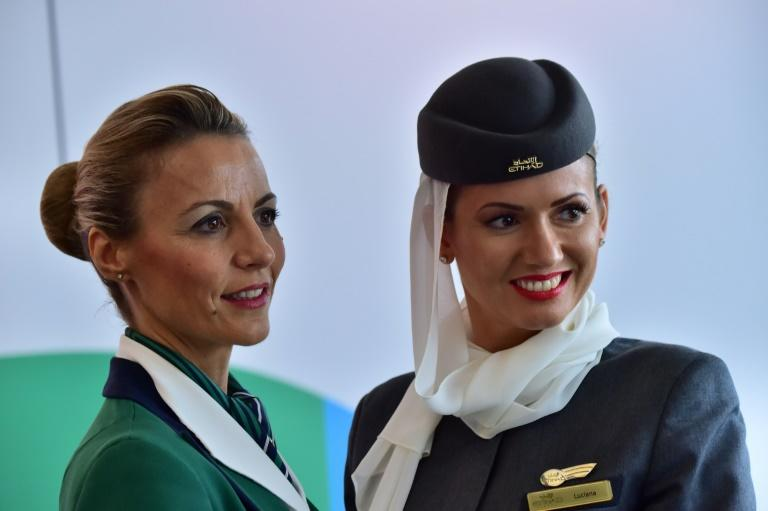 Hostesses of Italian company Alitalia (L) and Etihad Airways are pictured during a press conference to announce the partnership between Alitalia and Etihad in 2014