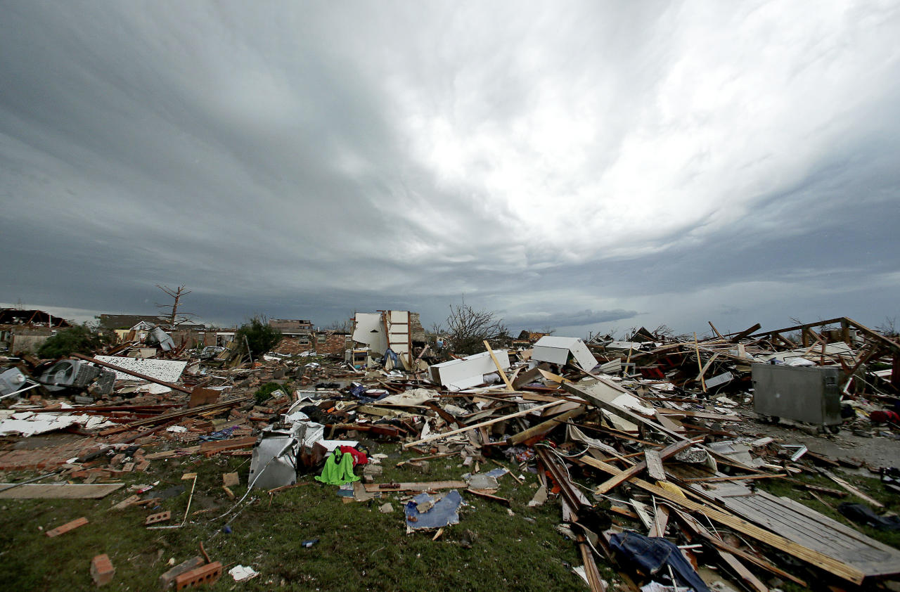 <p> Storm clouds build in the distance beyond tornado-ravaged homes Tuesday, May 21, 2013, in Moore, Okla. A huge tornado roared through the Oklahoma City suburb Monday, flattening entire neighborhoods and destroying an elementary school with a direct blow as children and teachers huddled against winds. (AP Photo/Charlie Riedel)