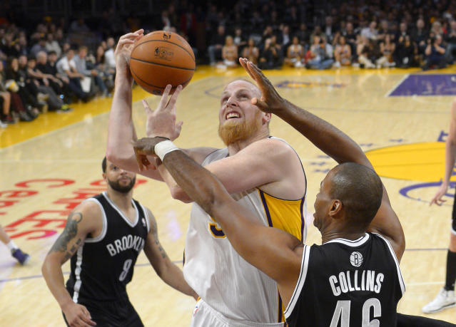 Los Angeles Lakers center Chris Kaman, center, puts up a shot as Brooklyn Nets center Jason Collins, right, defends and guard Deron Williams looks on during the second half of an NBA basketball game, Sunday, Feb. 23, 2014, in Los Angeles. The Nets won 108-102. (AP Photo/Mark J. Terrill)
