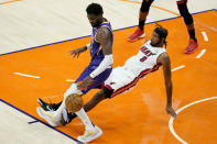 Miami Heat forward Trevor Ariza (8) fouls Phoenix Suns center Deandre Ayton during the first half of an NBA basketball game, Tuesday, April 13, 2021, in Phoenix. (AP Photo/Matt York)