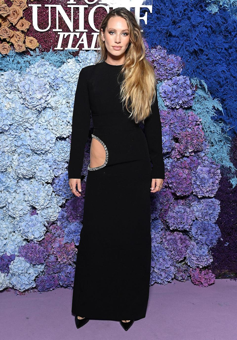 <p>in a long-sleeve black gown with embellished hip cutout, paired with pointy-toe pumps.</p>