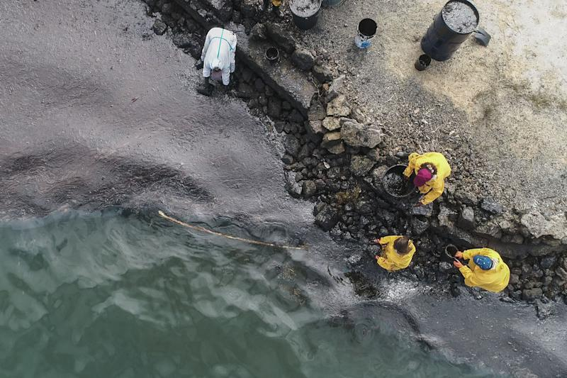 TOPSHOT - An aerial view shows people scooping leaked oil on August 10, 2020, from the MV Wakashio bulk carrier that had run aground at the beach in Bambous Virieux, southeast Mauritius. (Photo by - / L'Express Maurice / AFP) (Photo by -/L'Express Maurice/AFP via Getty Images)