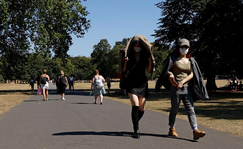 People shield themselves from the sun as they walk through Greenwich Park. (Photo: REUTERS)