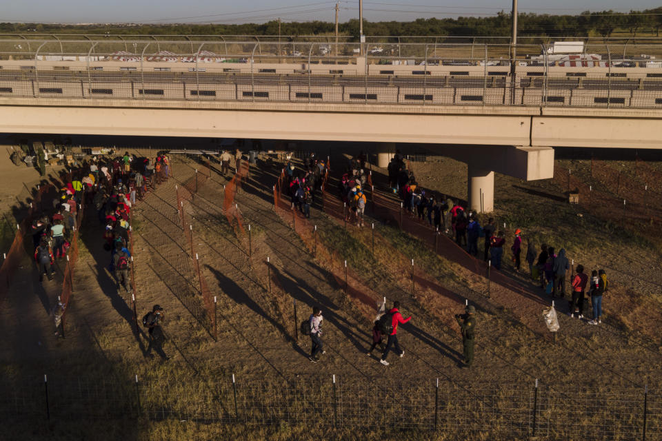Migrants, many from Haiti, are seen in lines waiting to board busses at an encampment along the Del Rio International Bridge near the Rio Grande, Thursday, Sept. 23, 2021, in Del Rio, Texas. (AP Photo/Julio Cortez)
