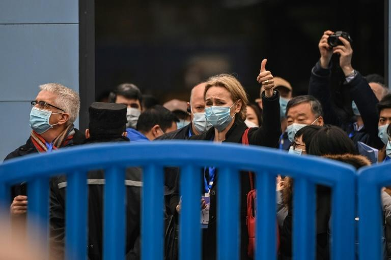 Thea Fisher (C) and other members of a WHO team investigating the origins of Covid-19 leave the Huanan Seafood wholesale market on Sunday