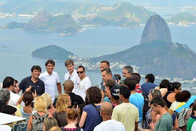 In this photo released by Fotojump, Spain's Rafael Nadal, top fourth from left, visits the Christ the Redeemer statue overlooking Sugar Loaf mountain, behind right, in Rio de Janeiro, Brazil, Saturday, Feb. 15, 2014. Nadal is in Brazil to play in the Rio Open ATP tournament. (AP Photo/Joao Pires, Fotojump)