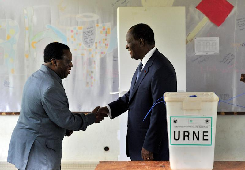 Ivory Coast's president Alassane Ouattara (R) shakes hands with Youssouf Bakayoko, the president of the Electoral Commission, after casting his vote at a polling station in Abidjan on April 21, 2013