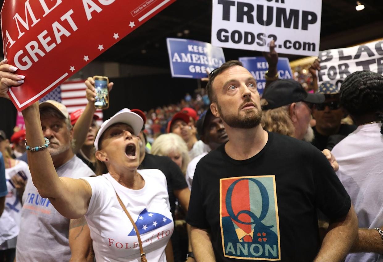 A man wear a shirt with the words QAnon as he attends a rally for President Donald Trump at the Make America Great Again Rally being held in the Florida State Fair Grounds Expo Hall on July 31, 2018, in Tampa, Florida.