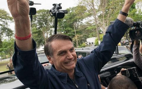Presidential frontrunner Jair Bolsonaro, of the Social Liberal Party, flashes victory hand signs to supporters after voting at a polling station in Rio de Janeiro - Credit: AP