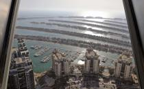 A portion of the Palm Jumeirah Island's frond villas and residential towers are seen from an observation deck of The View at The Palm Jumeirah, in Dubai, United Arab Emirates, Tuesday, April 6, 2021. Foreign buyers flush with cash have flooded the high-end property market in Dubai even as coronavirus vaccines roll out unevenly across the world and waves of infections force countries to extend restrictions. It's one of the few places in the world where they can dine, shop and do business in person. (AP Photo/Kamran Jebreili)