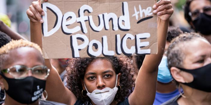 """A protester wears a mask and holds a homemade sign that says """"Defund the Police"""" at a demonstration on June 19, 2020, in New York City."""