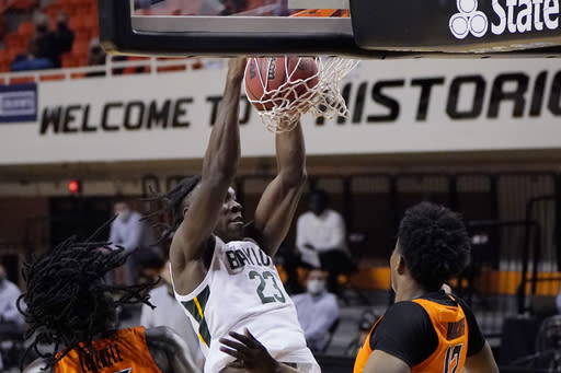 Baylor forward Jonathan Tchamwa Tchatchoua (23) dunks between Oklahoma State guard Isaac Likekele, left, and forward Matthew-Alexander Moncrieffe, right, in the first half of an NCAA college basketball game Saturday, Jan. 23, 2021, in Stillwater, Okla. (AP Photo/Sue Ogrocki)