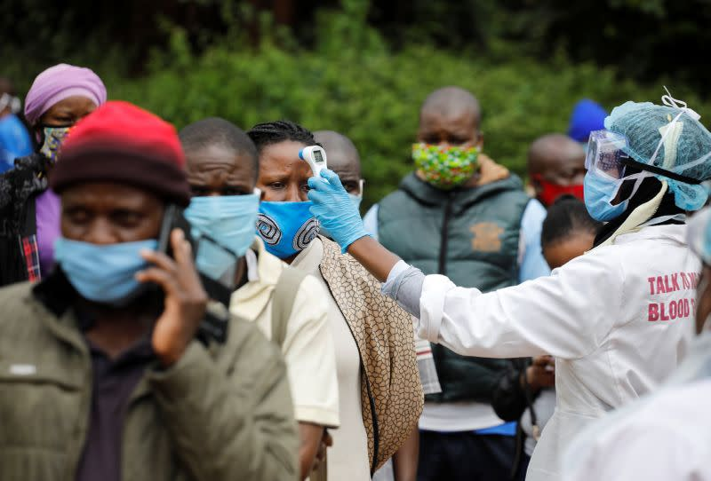 A health worker takes the temperature of a person standing in line for mass testing in an effort to stop the spread of the coronavirus disease (COVID-19) in the Kibera slum of Nairobi