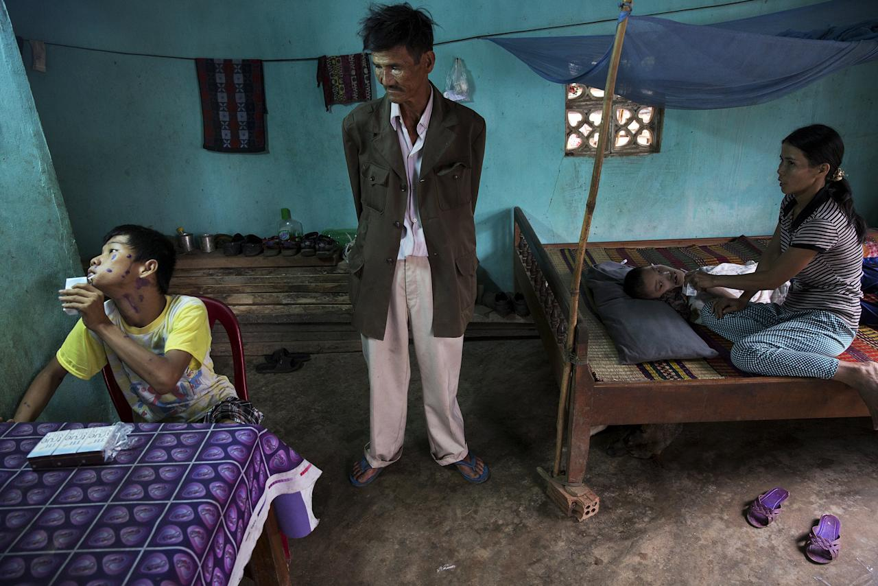 """Le Van Dan (C) looks at his disabled grandson Le Van Tam (L) as his daughter feeds another sick grandson in their family house in Phuoc Thai village, outside Danang April 12, 2015. Le Van Dan, a former artillery soldier with the South Vietnamese army, said he was exposed to Agent Orange more than once, including being directly sprayed by U.S. planes near his village before he joined the military. Health officials confirmed two of his grandsons' disabilities are due to his exposure to the defoliant, Le Van Dan said. REUTERS/Damir Sagolj  PICTURE 21 OF 24 FOR WIDER IMAGE STORY """"VIETNAM: LEGACY OF AGENT ORANGE""""SEARCH """"AGENT SAGOLJ"""" FOR ALL IMAGES  TPX IMAGES OF THE DAY           TPX IMAGES OF THE DAY"""