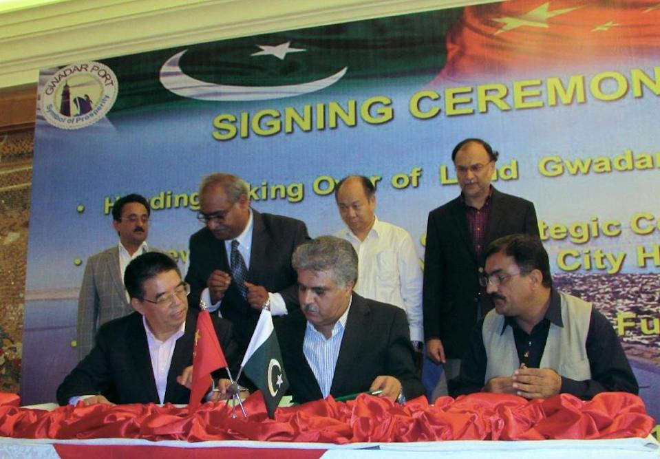 Chairman of Pakistan's Gwadar Port Authority, Dostain Khan Jamaldini (C) and chairman of China Overseas Port Holding Company, Zhan Baozhang (L) sign an agreement during a ceremony in the Gwadar port city of Baluchistan province on November 11, 2015 (AFP Photo/Bahram Baloch)