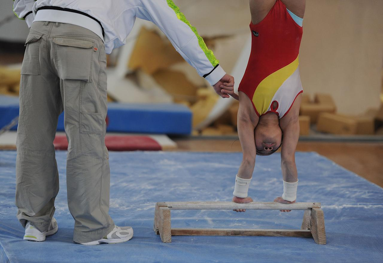 In a photograph taken on April 7, 2012, a young Chinese gymnast trains at a special sport school in Hefei, east China's Anhui province. Potential gymnasts embark on a gruelling schedule which aims to create champions, as schooling and family take a back seat to eight hours of training six days a week, while quitting the rigid system that demands total dedication, and in which the state invests millions of dollars to develop its athletes, is rarely an option.          CHINA OUT      AFP PHOTO (Photo credit should read AFP/AFP/Getty Images)