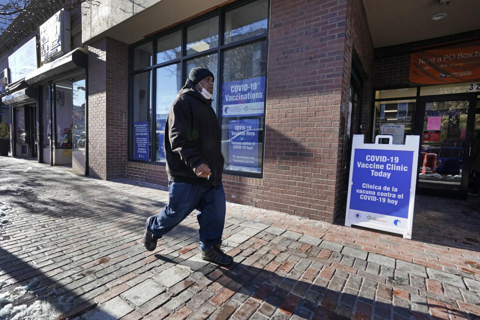 A man walks by the recently opened COVID-19 vaccination site in Chelsea, Mass. Feb. 8, 2021. Chelsea's vaccination sites are limited by Massachusetts' eligibility rules, which only recently expanded to persons 65 or older, as well as people with two or more serious medical conditions. (AP Photo/Elise Amendola)
