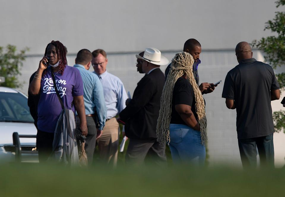 A Smile Direct employee uses her phone as Metro Police investigate a shooting after an employee opened fire and shot three other employees at the Smile Direct Club warehouse Tuesday, Aug. 3, 2021 in Nashville, Tenn.