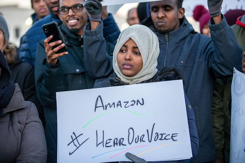 Demonstrators shout slogans and hold placards during a protest at the Amazon fulfillment center in Shakopee, Minnesota, on December 14, 2018. - A group of Amazon workers in Minnesota who are Somali refugees resettled in the Midwestern US state demanded better working conditions during a protest outside one of the retailer's warehouses. Dozens braved frigid temperatures to demonstrate outside of the Amazon warehouse in the Minneapolis suburb of Shakopee -- home to a sizable Somali immigrant population from which Amazon has heavily recruited. (Photo by Kerem Yucel / AFP) (Photo credit should read KEREM YUCEL/AFP/Getty Images)