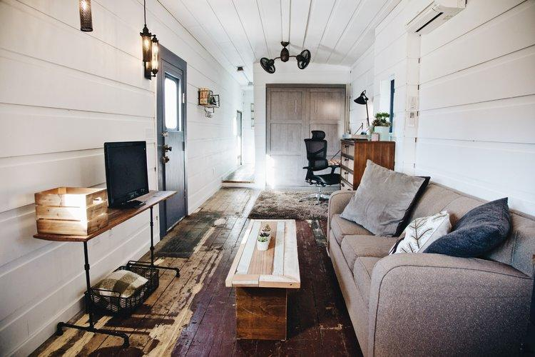 Adrienne decided against the black Sherwin Williams paint she bought to cover the original dark-rust floors, and let the floor's character bleed through. Photo credit: Airbnb.