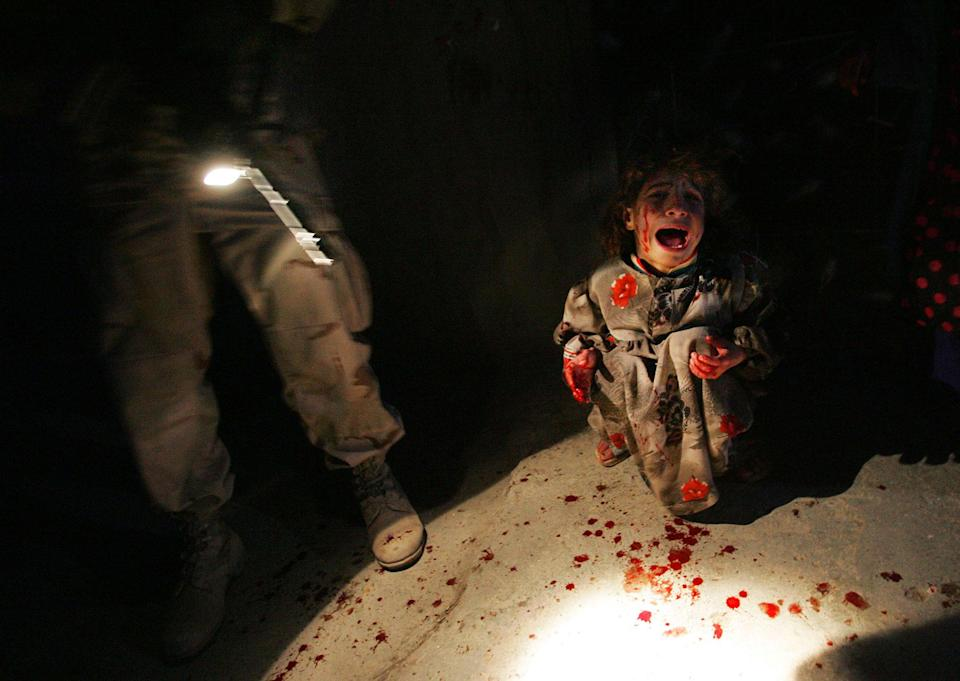 <p>Samar Hassan, 5, screams after her parents were killed by U.S. Soldiers with the 25th Infantry Division in a shooting January 18, 2005 in Tal Afar, Iraq. The troops fired on the Hassan family car when it unwittingly approached them during a dusk patrol in the tense northern Iraqi town. Parents Hussein and Camila Hassan were killed instantly, and a son Racan, 11, was seriously wounded in the abdomen. Racan, paralyzed from the waist down, was treated later in the U.S. (Photo by Chris Hondros/Getty Images) </p>